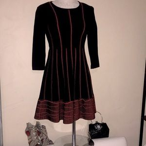 D. Exterior black and red dress w/ pleated stripes
